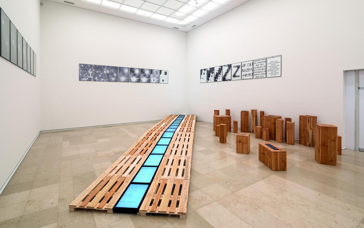 Auf einer längeren Reihe aus Paletten liegen mittig monochrome Bildschirme. Rechts stehen einzelne kleine Klötze. An den Wänden hängen kleine quadratische Poster mit abstrakten Motiven.