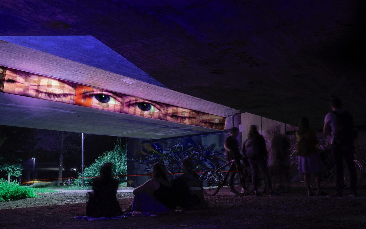 A bridge in a park at night. A row of pairs of eyes is projected in a horizontal strip on the outer wall of the bridge. The rets of the bridge shine in different colors.