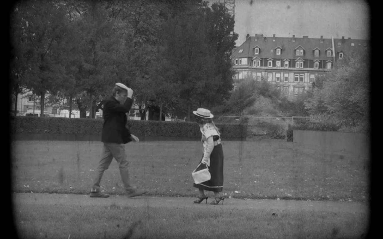 """Two pedestrians meet on the street, the man is lifting his heat as to greet the Woman, that is aproaching. It is a still from a black-and-white movie made in the workshop """"the little rascals""""."""