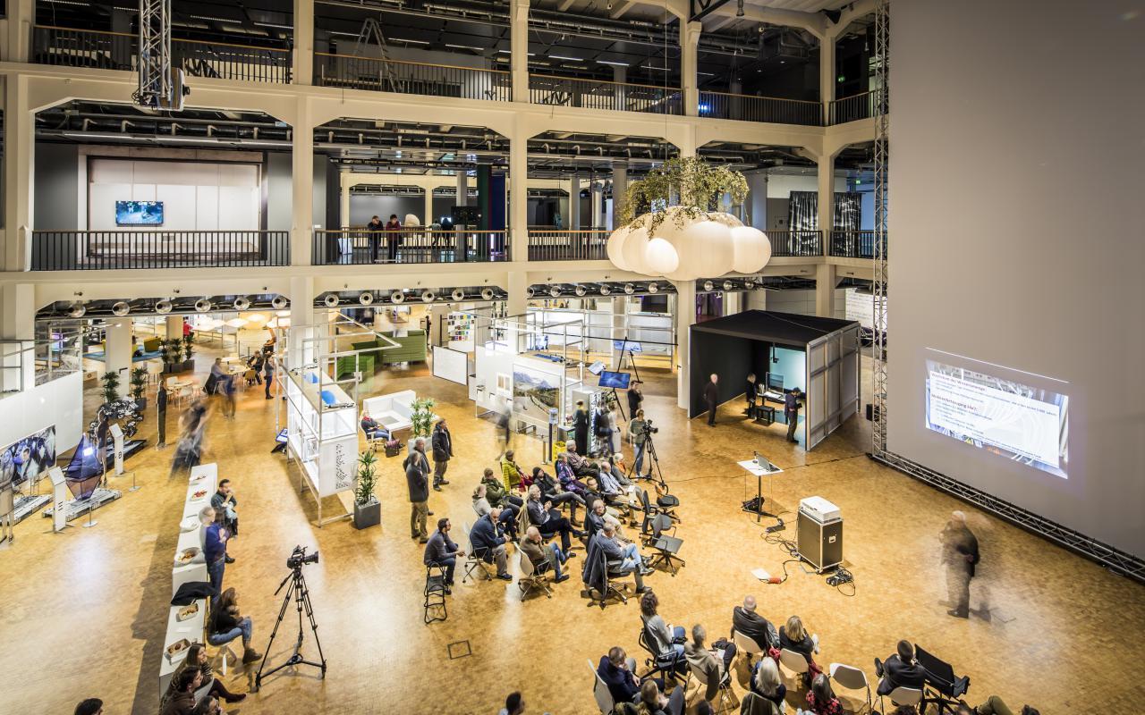 Das Bild zeigt das mit Menschen gefüllte OpenHub der Ausstellung »Open Codes«
