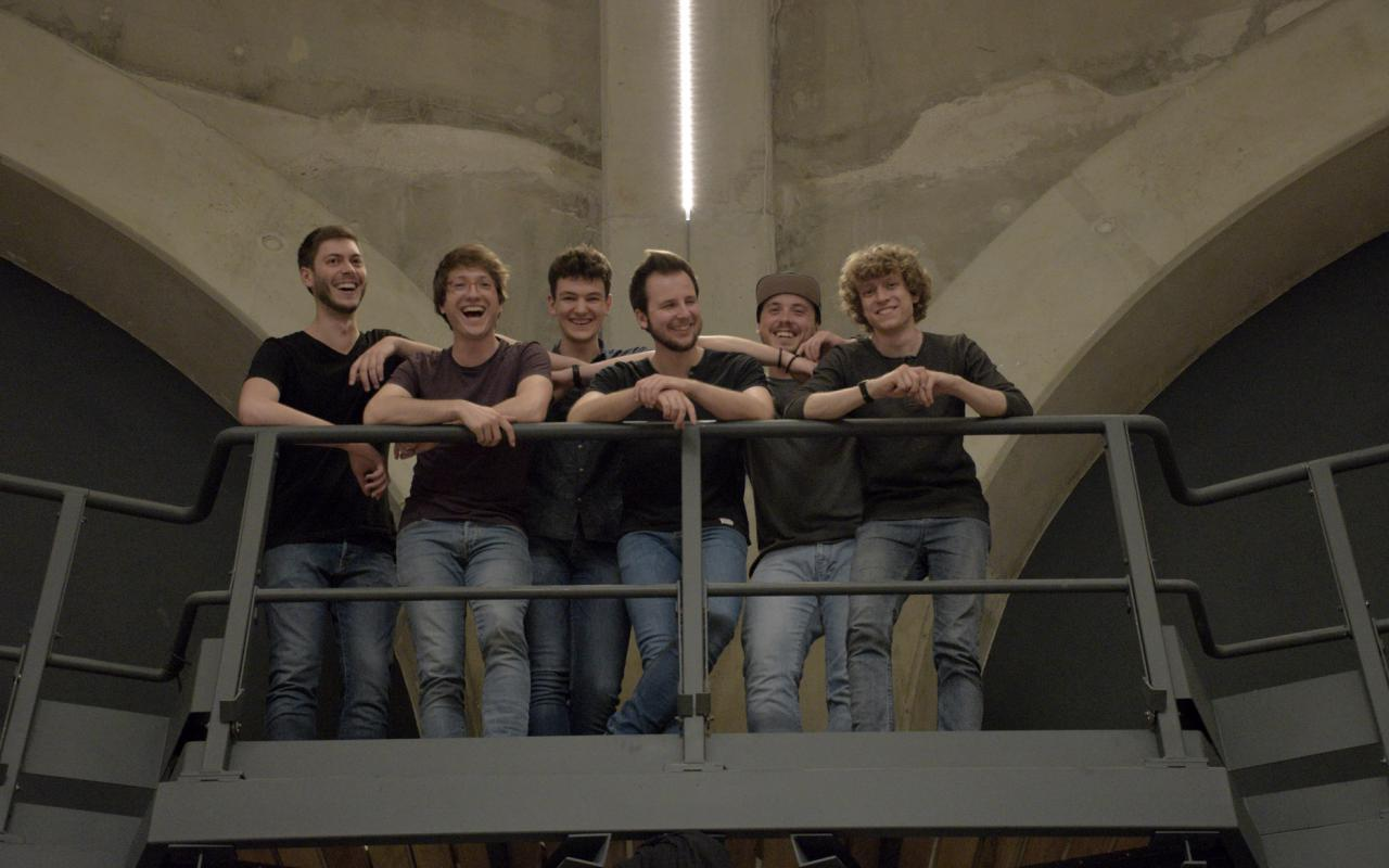 The six members of the band »Open Source Guitars«, leaning against a railing.