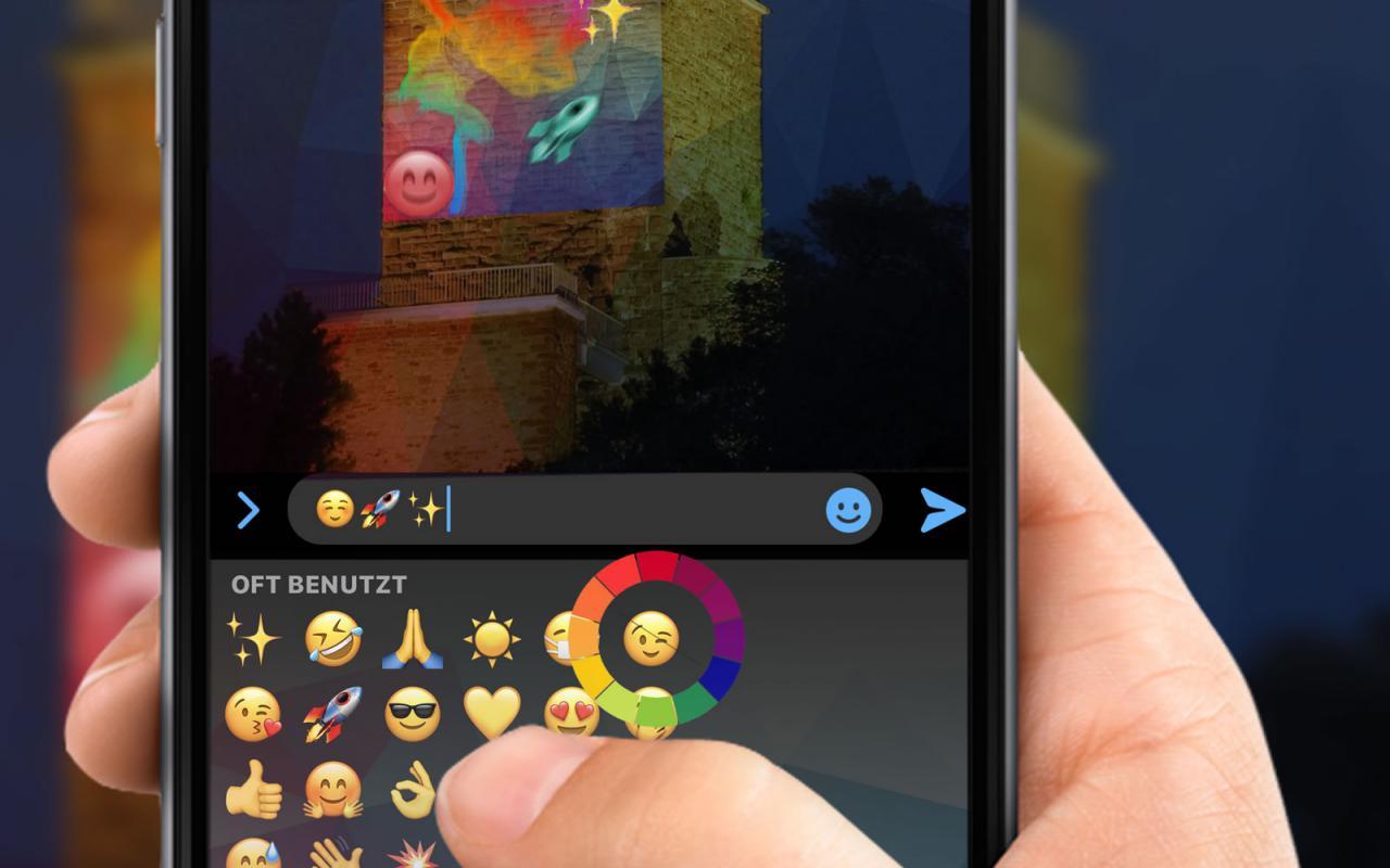 Zu sehen ist eine Hand, die mit dem Handy auf einen Turm zeigt. Auf dem Display werden mehrere Emojis angezeigt, die nach einem Klick auf dem Turm zu sehen sind.