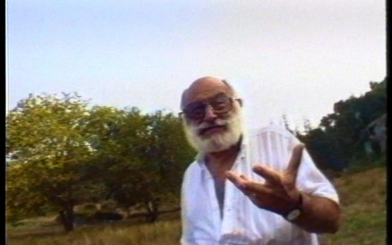 Mean with beard in a white shirt talks into the camera. It is Vilém Flusser