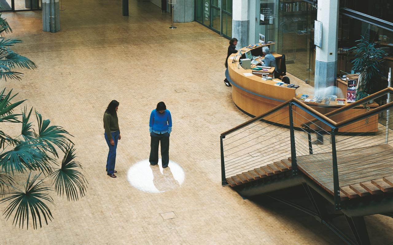 Zu sehen ist das Foyer des ZKM. Zwei Personen stehen in der Nähe der Treppe und des Infostandes. Um eine der Personen ist auf dem Boden ein Lichtkreis zu sehen.
