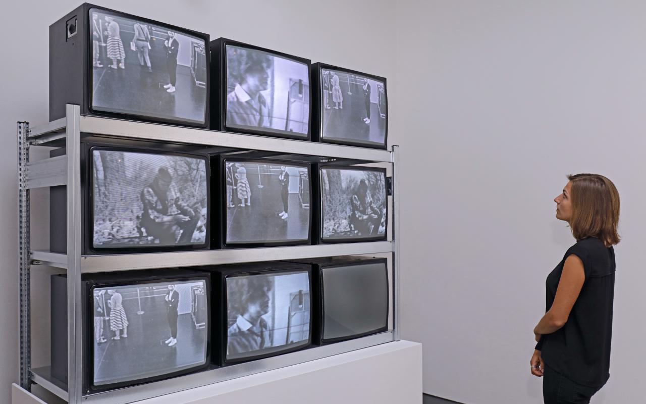 Besucherin vor einer Installation aus neun Fernsehbildschirmen,
