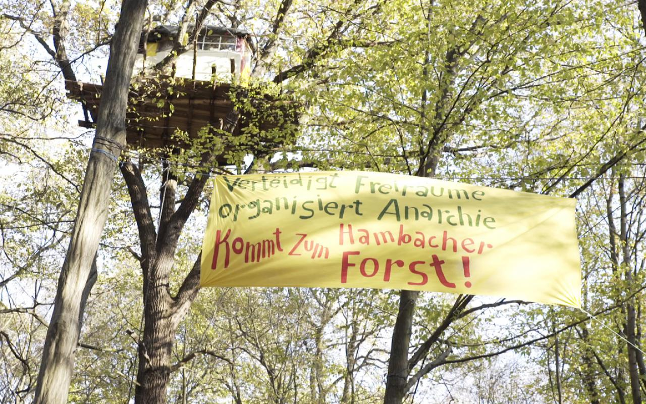 You can see a tree house. Below the tree house there is a banner stretched between the trees which reads: »Defend open spaces. Organizes anarchy. Come to the Hambach Forest!«
