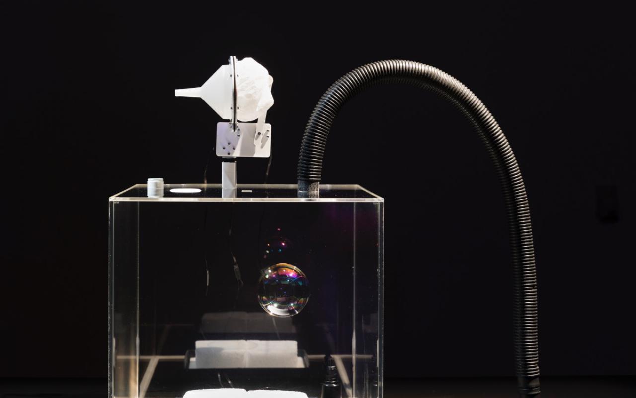 Ein Staubsaugerrohr mündet in einen quadratischen Glasquader, auf dem eine Installation angebracht ist.
