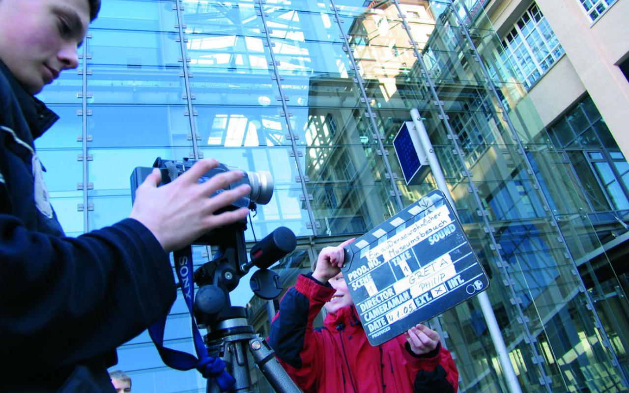 Jemand bedient eine Filmkamera, die auf einem Stativ steht. Ein anderer hält eine Filmklappe vor die Kamera