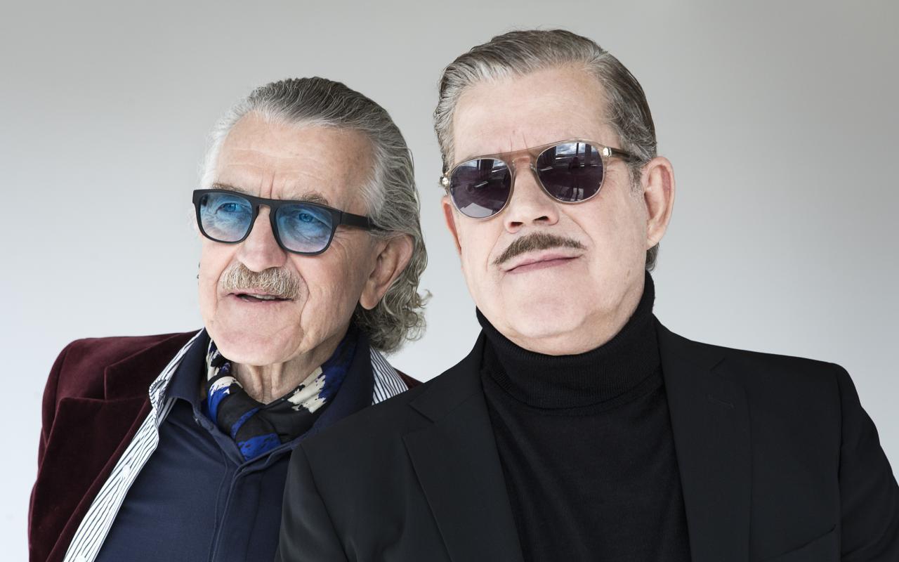 Zwei Männer stehen nebeneinander, die beiden Köpfe sind groß zu sehen. Der rechte trägt eine Sonnenbrille, einen Oberlippenbart, kurze, nach hinten gekämmte Haare und einen Rollkragen mit Jacket. Der linke trägt eine gefärbte Sonnenbrille.