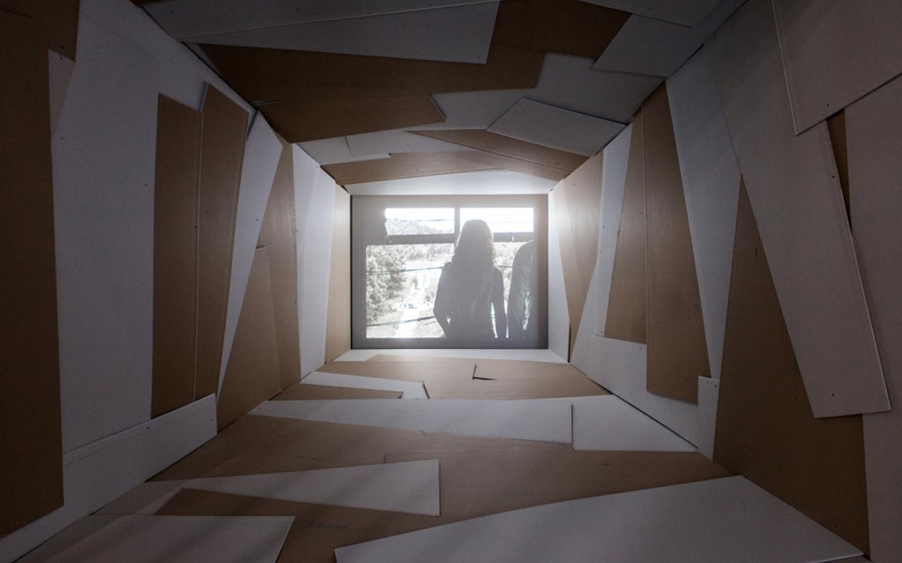 Am Ende eines rechteckigen Tunnels sieht man ein helles Bild mit der Silhouette einer Frau.