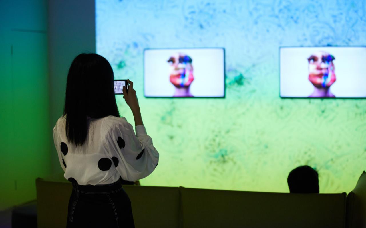 Das Foto zeigt die Arbeit »im here to learn so :))))))«. Im Hintergrund ist eine große Leinwand auf der ein Google DeepDream projiziert ist. Drei davor liegende Bildschirme zeigen den Kopf des Chatbots Tay.