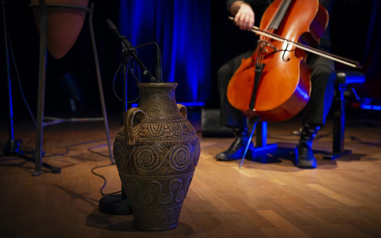 Zu sehen ist eine braune, verzierte Vase im Zentrum und rechts dahinter ein Person am Cello