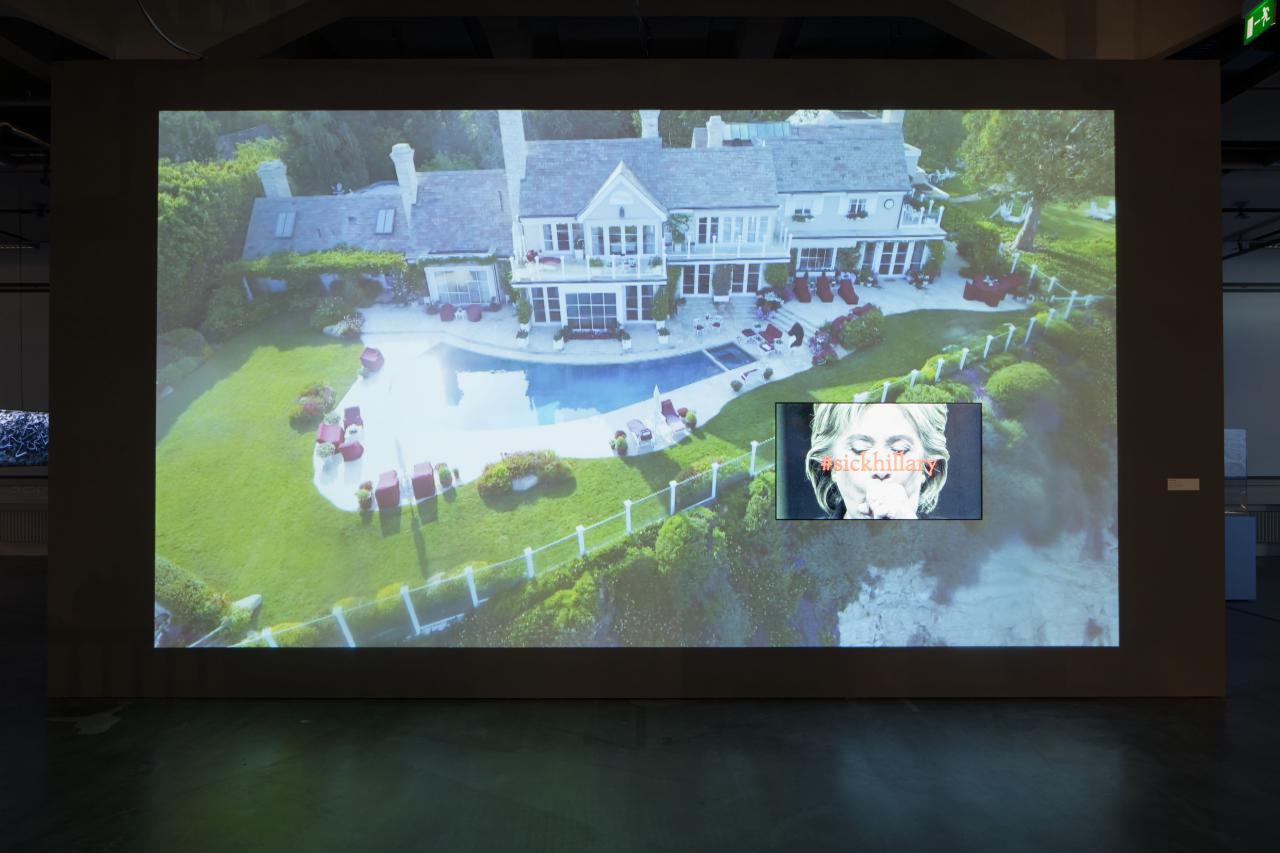 Auf einer Videoleinwand ist eine Villa mit Pool und ein Bild von Hillary Clinton unter dem »sickhillary« steht, zu sehen.