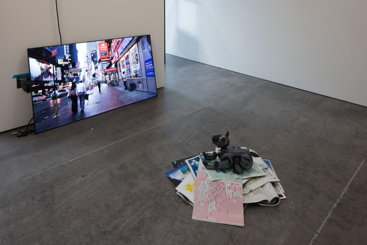 A roboter dog sits on a pile of books and magazines while he looks at a screen.