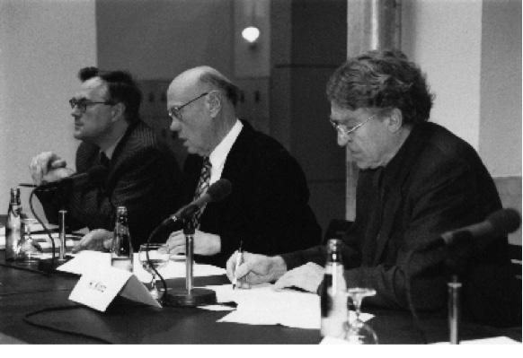 Schwarz-weiß Fotografie von drei Männern an einem Tisch