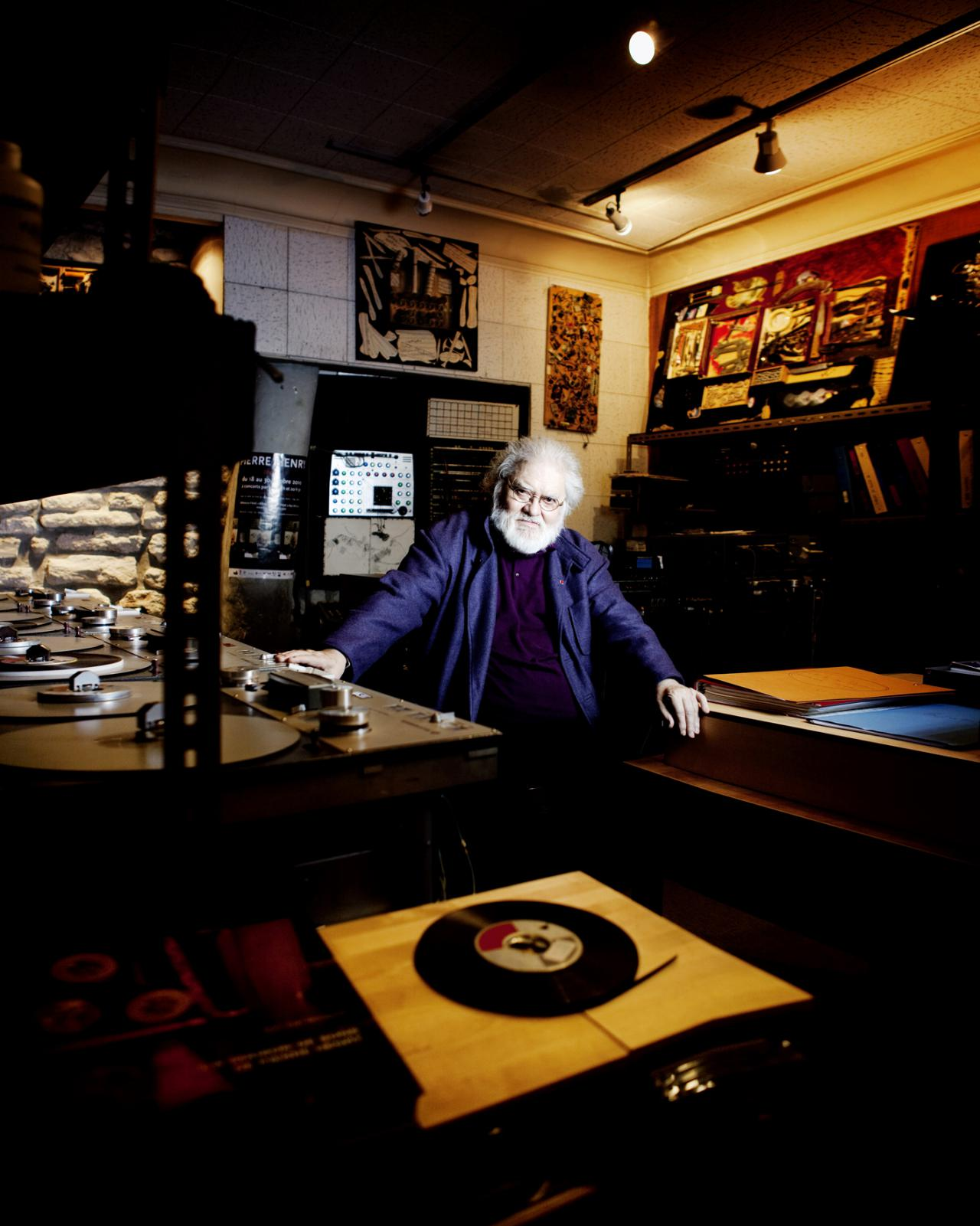 A man sits amid several turntables