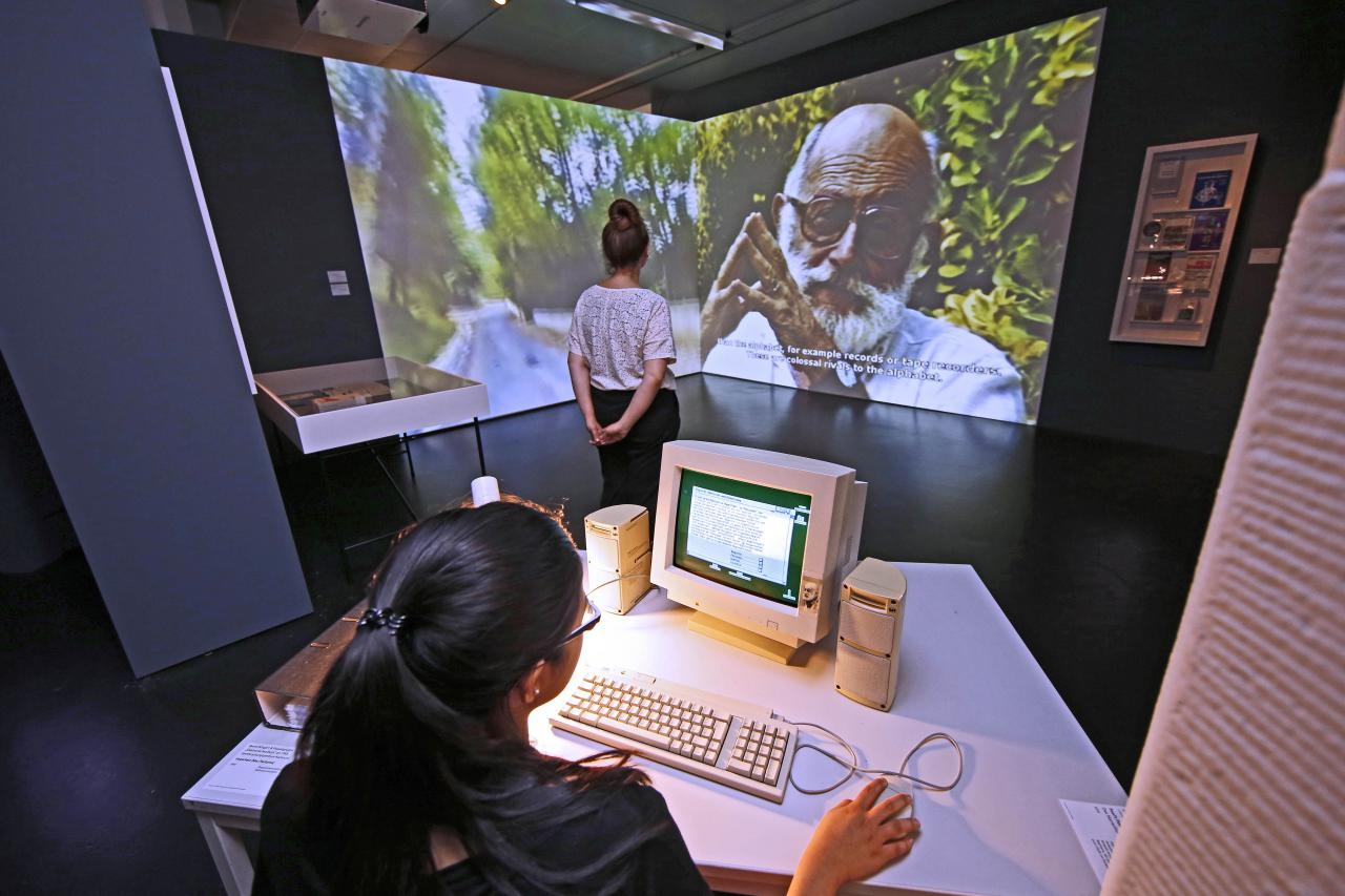 Ausstellungsansicht: ein Mädchen am Computer, im Hintergrund eine wandfüllende Videoprojektion mit Vilém Flusser