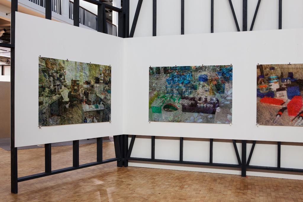 Drei großformatige Bilder an der weißen Wand.
