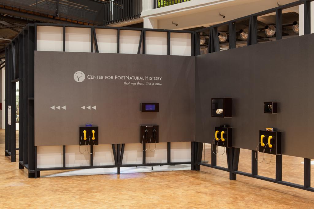 Schaukästen und Telefonhörer an einer grauen Wand. Die Wand trägt einen Schriftzug, Pfeile verweisen auf einen anderen Ort.
