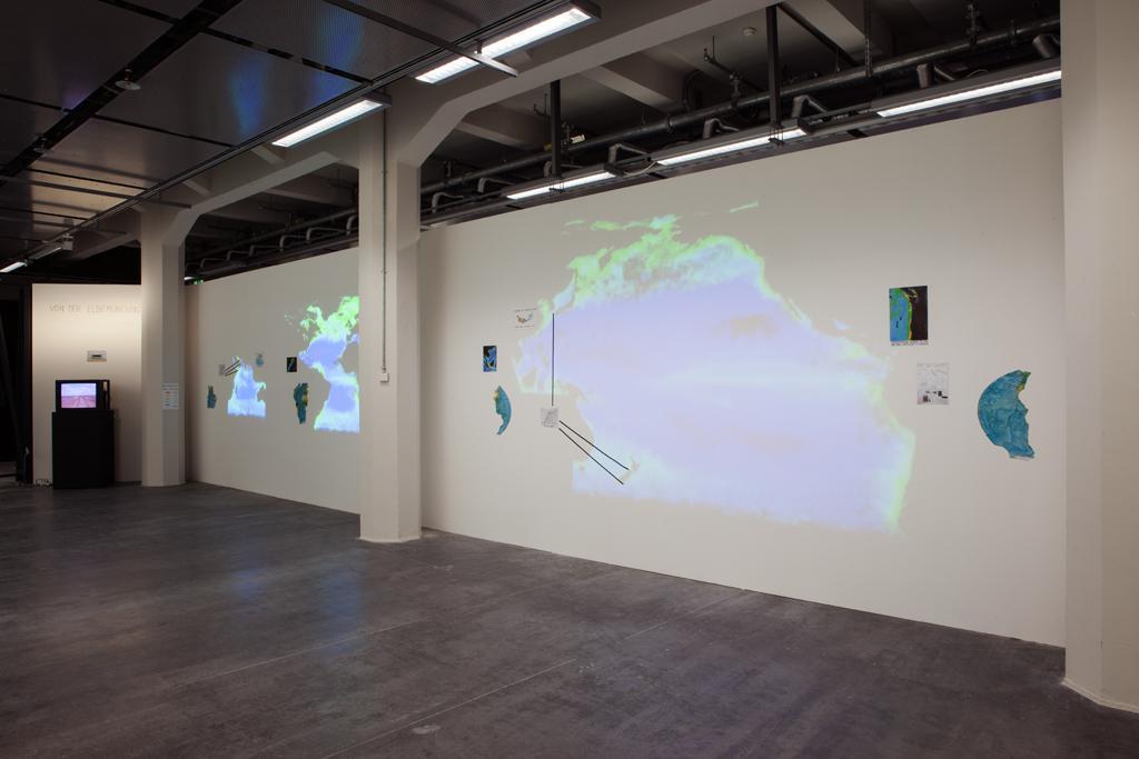 Kartenwerk Fragmente auf einer weißen Wand, darauf Projektionen geografischer Bilder.