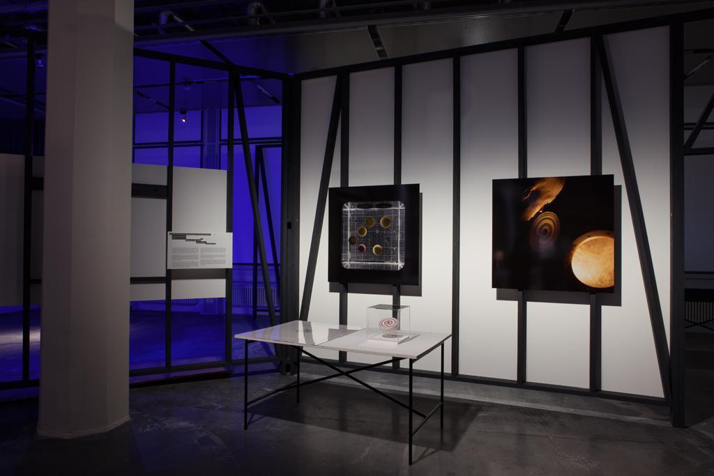 Zwei Drucke im Hintergrund, ein Tisch mit Exponaten im Vordergrund.