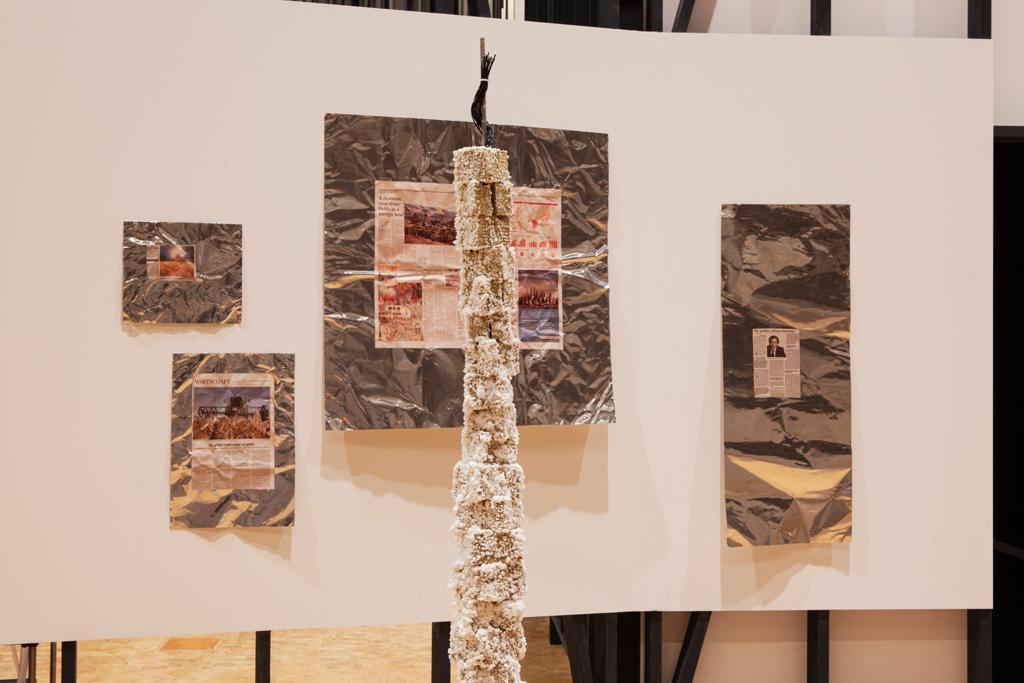 Zeitungsausschnitte auf Metallfolie vor einer weißen Wand, eine säulenartige Skulptur im Vordergrund.