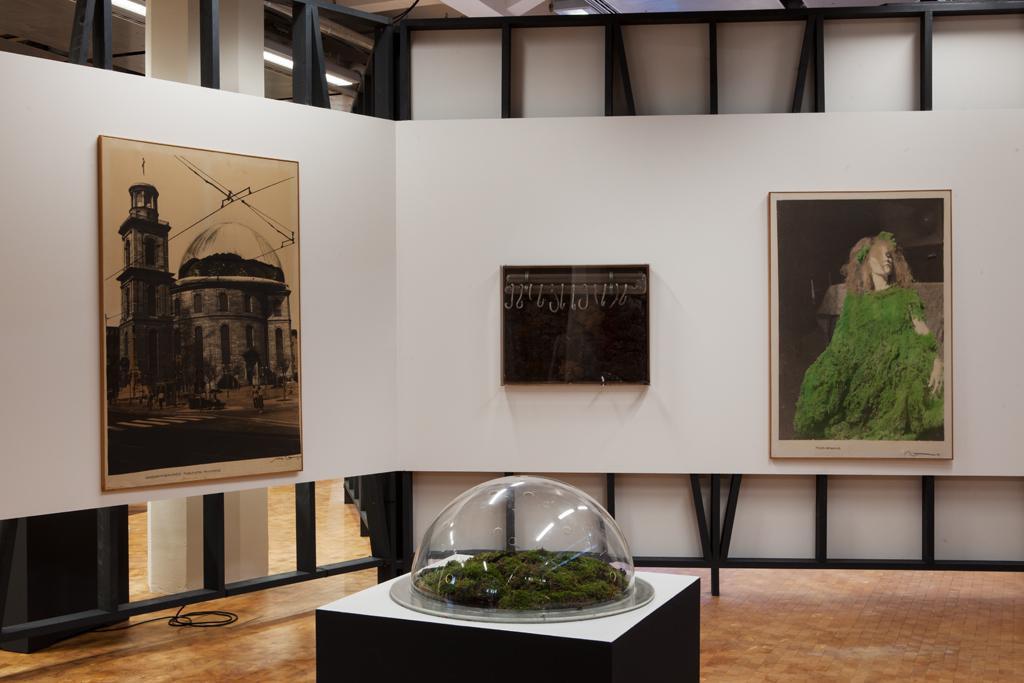 Drei Bilder an der weißen Wand, im Vordergrund steht ein 3D Modell unter einer Glashaube auf einem Sockel.