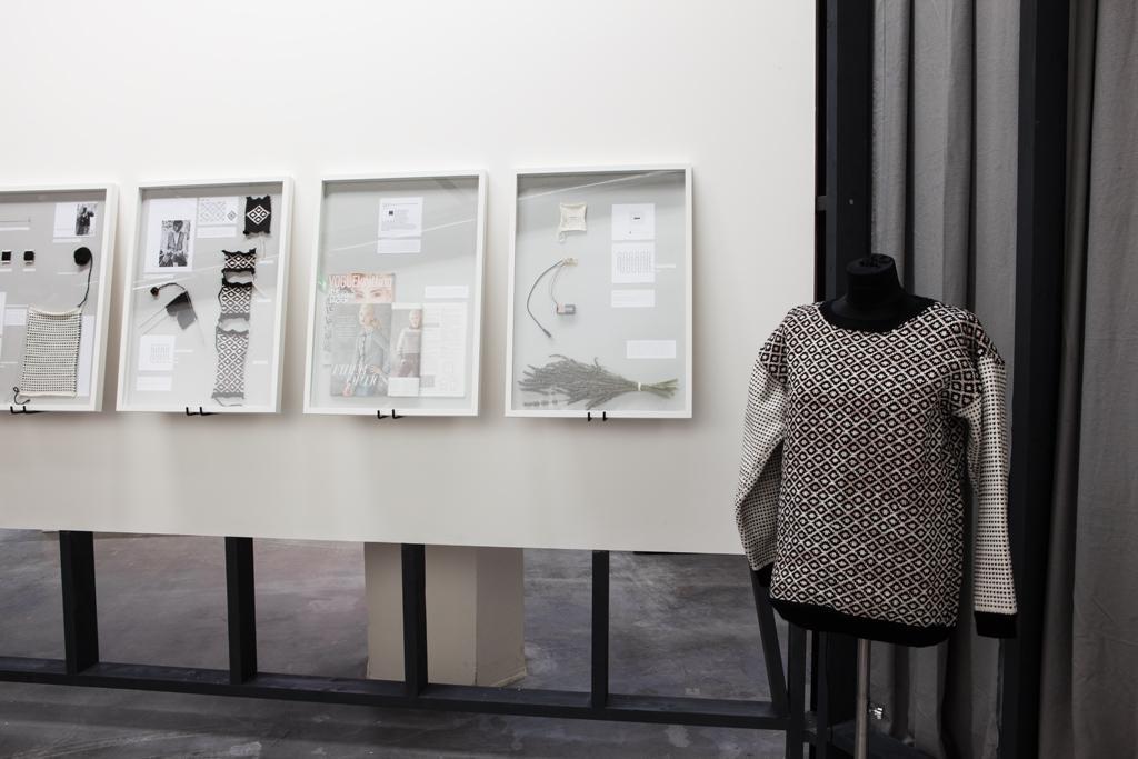 Vier Schaukästen hängen an einer weißen Wand, daneben steht eine Kleiderpuppe, sie trägt einen gestrickten Pullover.