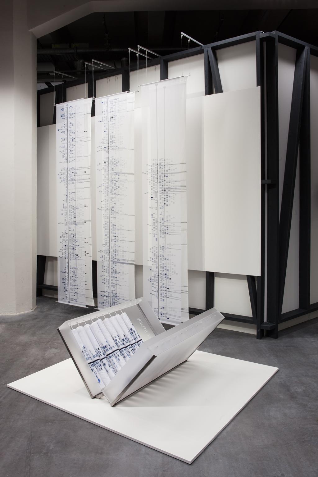 Auf einer weißen Bodenplatte steht ein kofferartiger Behälter mit Textilrollen. Im Hintergrund hängen drei Textilbanner mit darauf abgebildeten Infografiken.