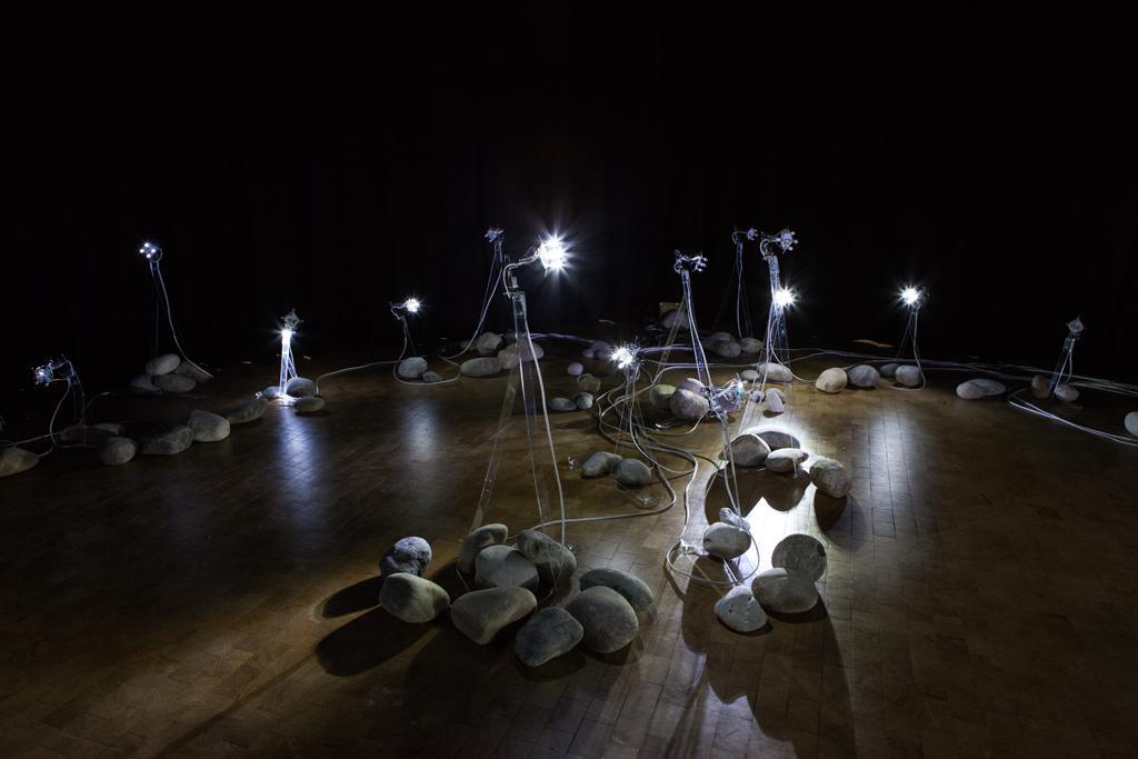 Große Kieselsteine liegen gruppiert auf dem Boden dazwischen ragen Leuchtelemente empor.
