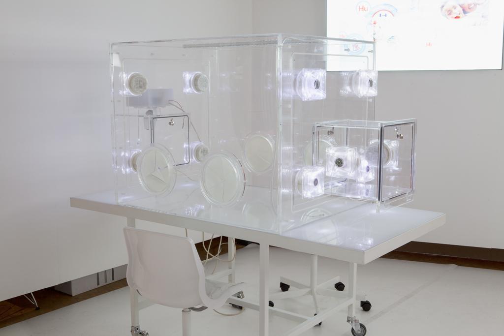 Leerer Baby Brutkasten auf einem rollbaren weißen Tisch. Zwei weiße Stühle stehen an dem Tisch, im Hintergrund läuft eine Projektion auf der weißen Wand.