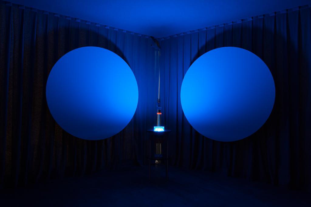 Zwei kreisrunde Flächen hängen in einem neunzig grad Winkel zueinander. Dazwischen befindet sich ein Gefäß auf einer Stellage von dem blaues Licht ausgeht.