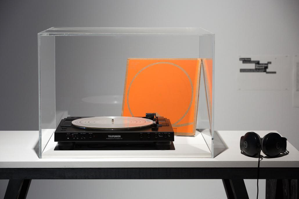 Ein alter Plattenspieler und eine orangene Plattenhülle in einer Vitrine