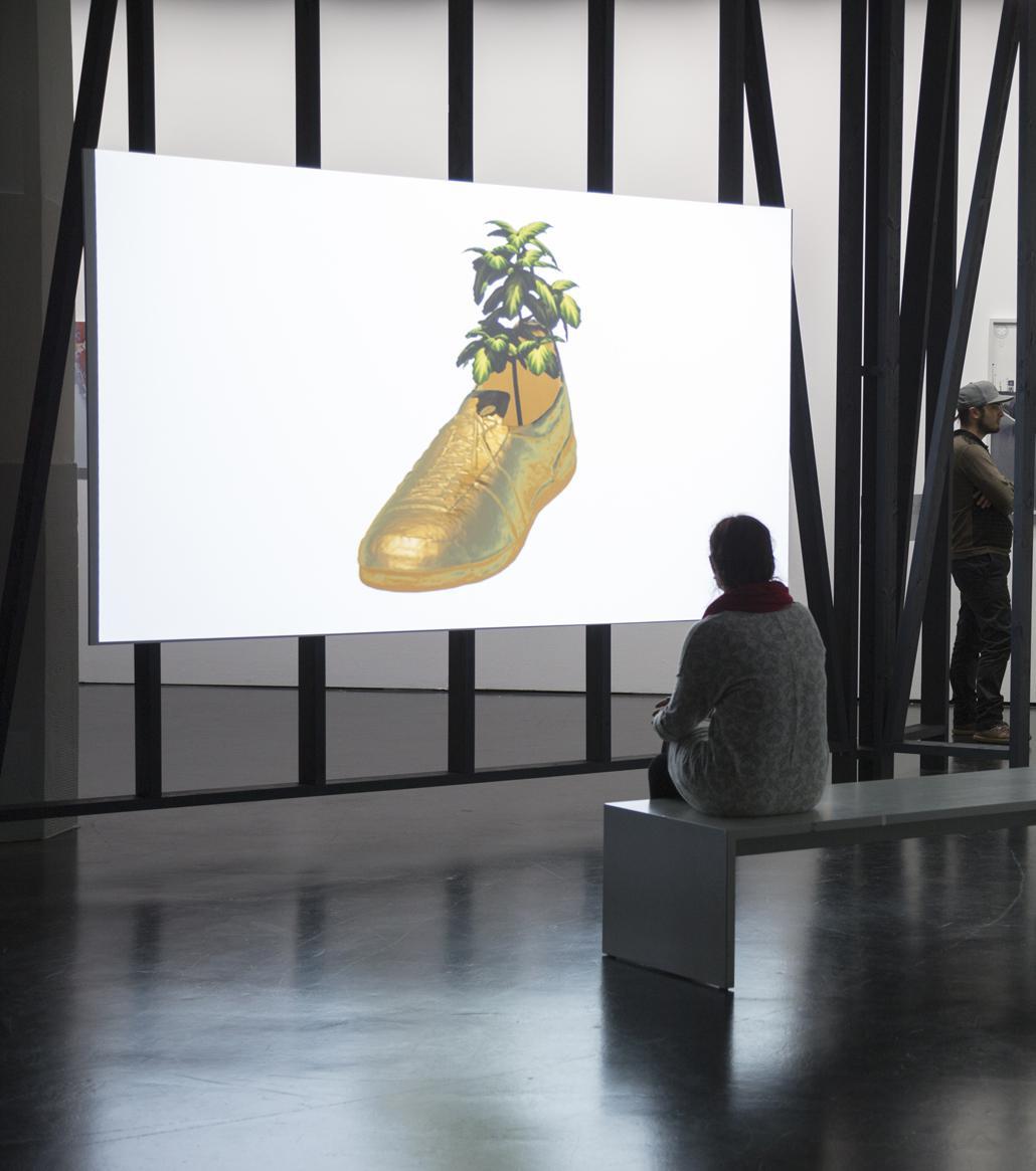 Ein gemalter goldener Schuh, aus dem eine Palme wächst