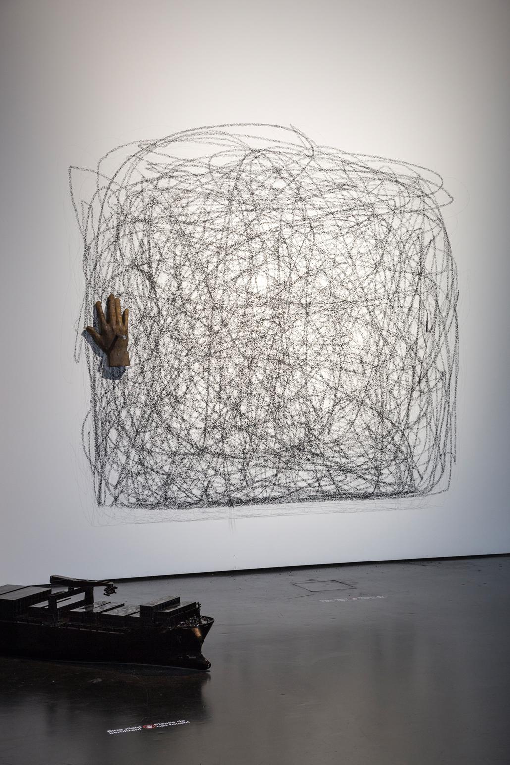 Eine bekritzelte Wand. Daneben hängt ein Handschuh
