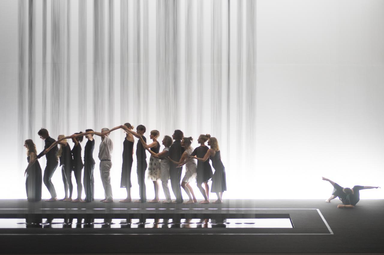 Performance bei der die Tänzer in einer Schlage stehen und mit den Armen eine Welle bilden.