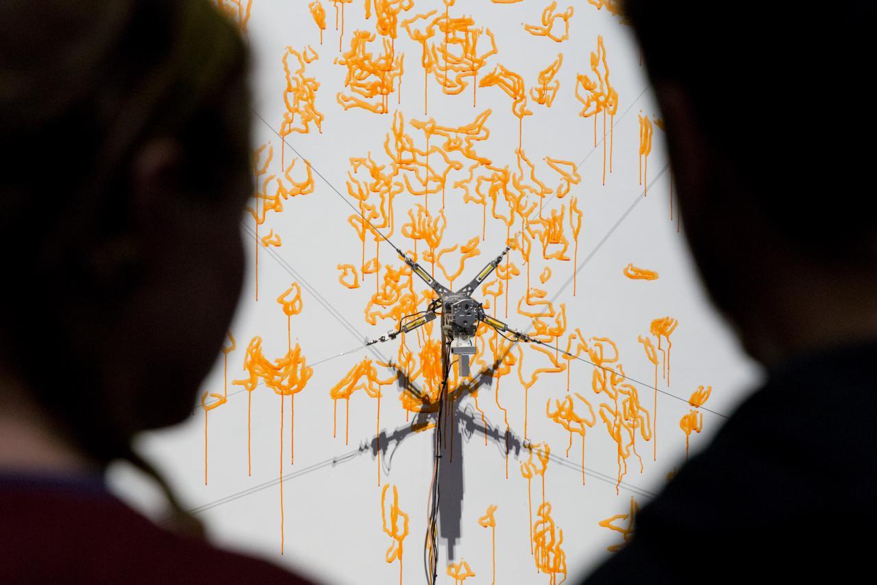 Zwei Silhouetten blicken auf den computergesteuerten Malroboter, der mit gelber Farbe auf eine Leinwand malt.