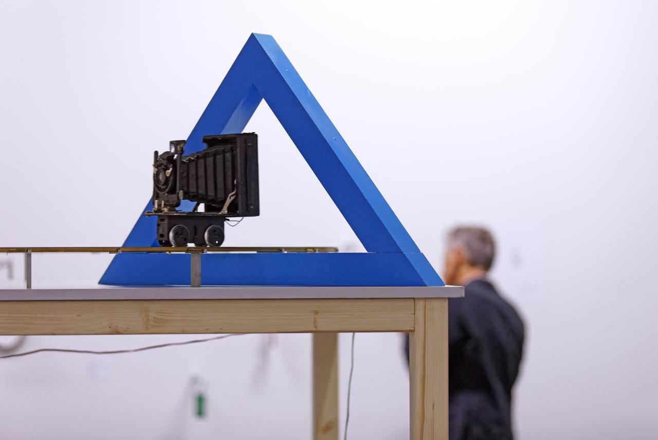 Das Bild zeigt eine Kamera, die durch ein hohles, blaues Dreieck gerichtet ist.