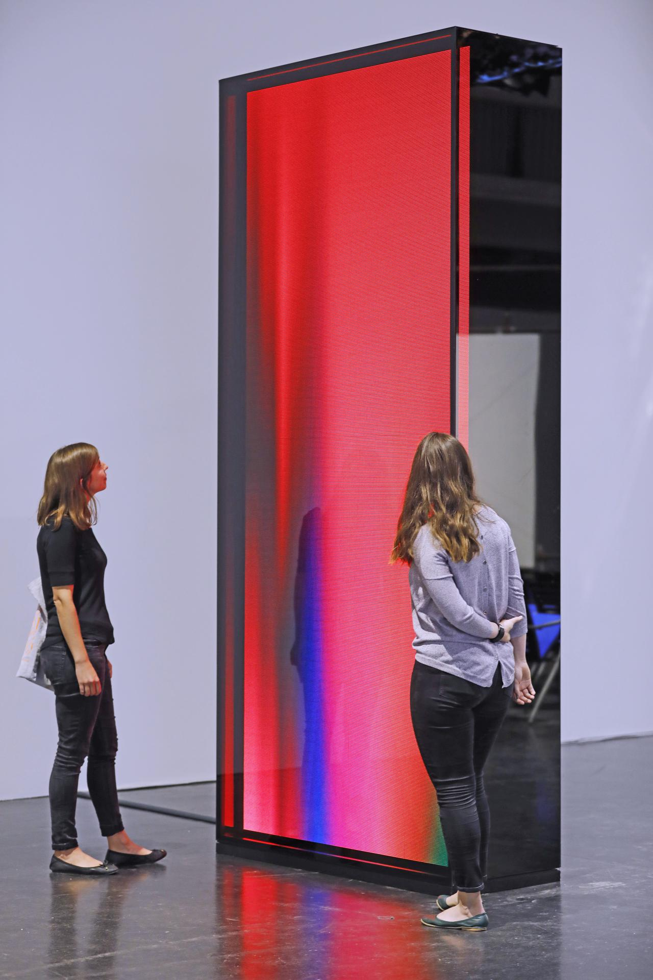 "Visitors in front of a 3.5m high reddish ""cosmic"" light sculpture."