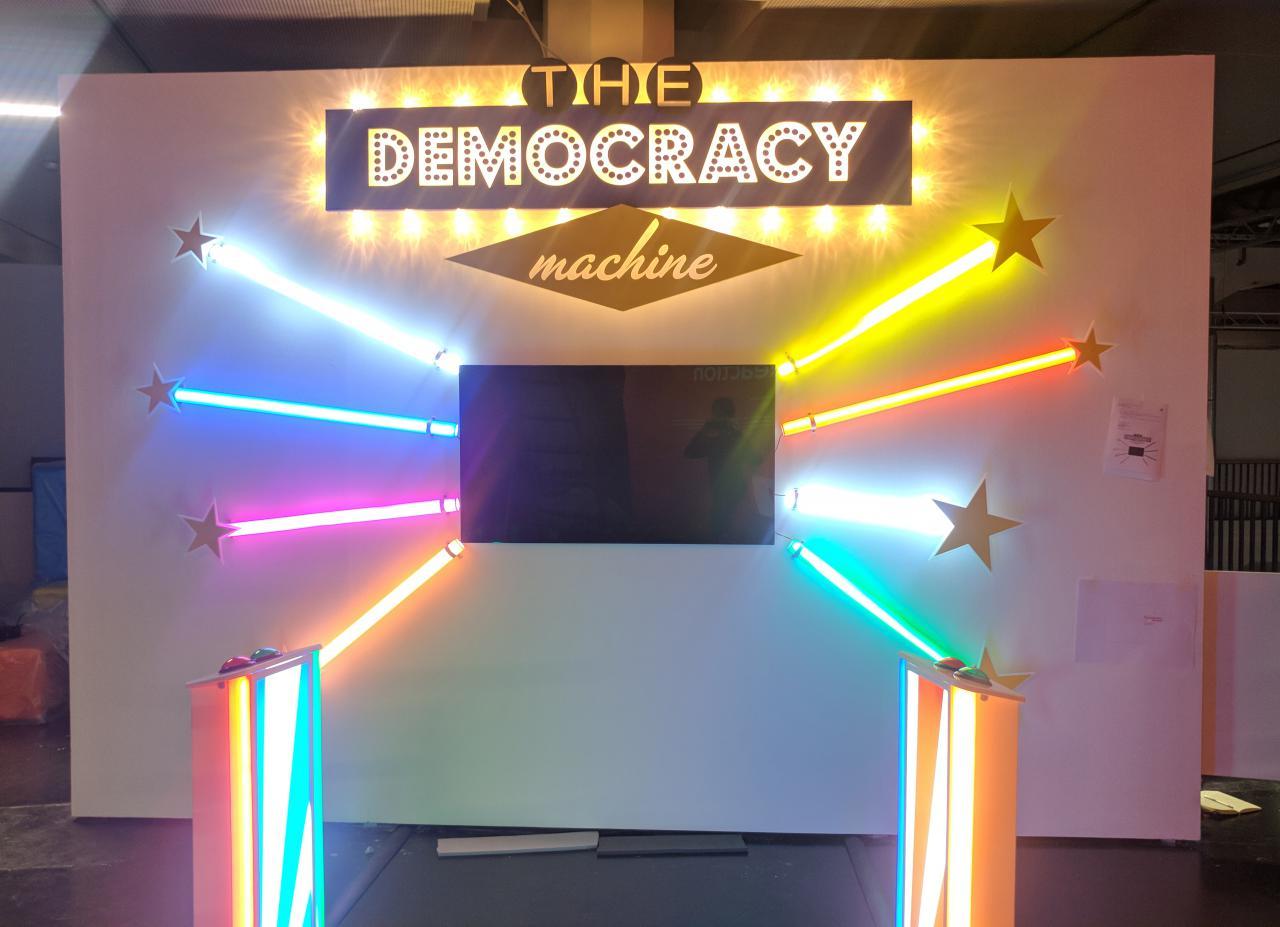 Frontalansicht der The Democracy Machine!. In der Mitte einer Wand ist ein Fernseher installiert darum herum sind je drei bunte Farbröhren wie Sonnenstrahlen angeordnet. Davor stehen zwei Podeste mit Knöpfen.