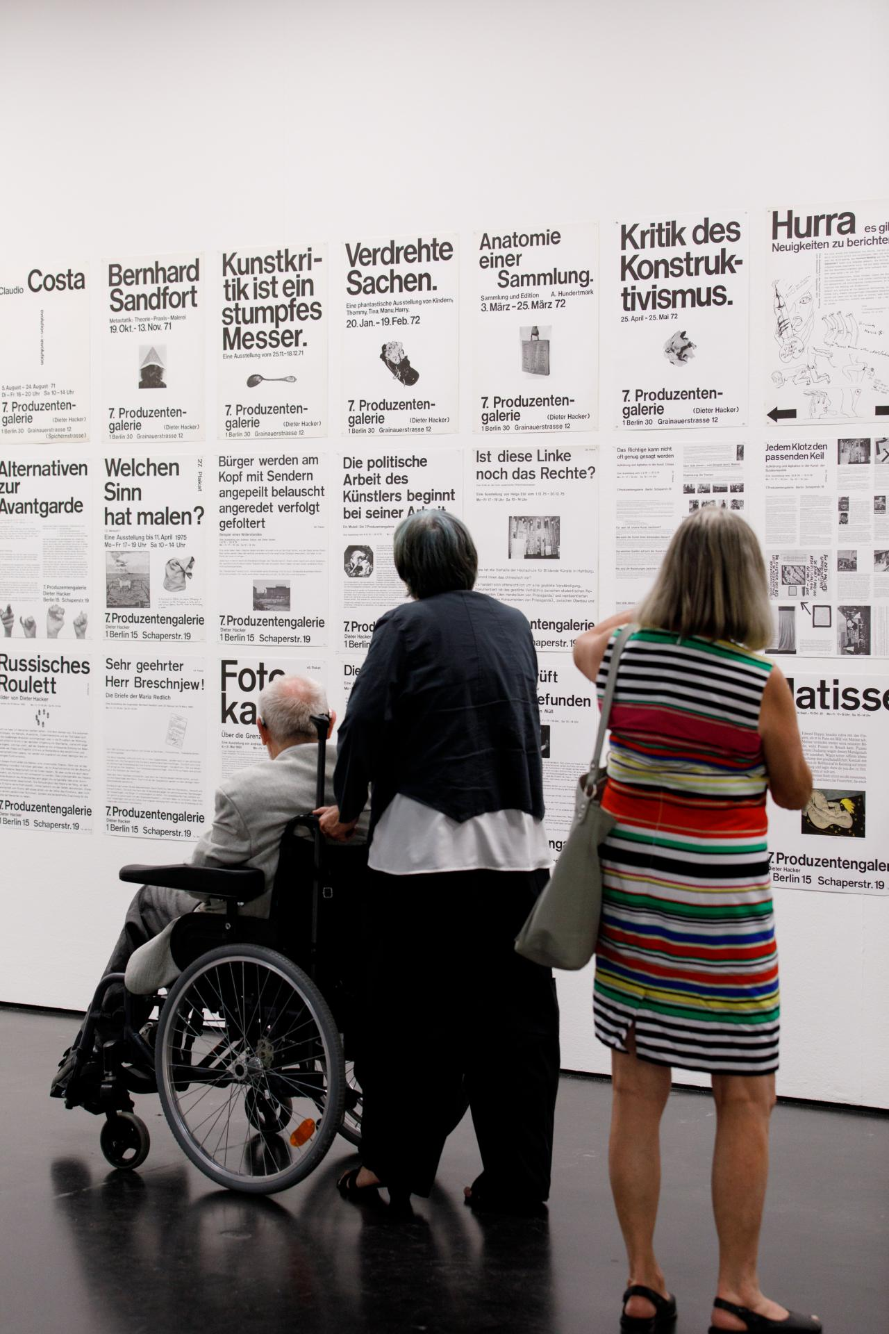 The picture shows three visitors in front of posters with typography