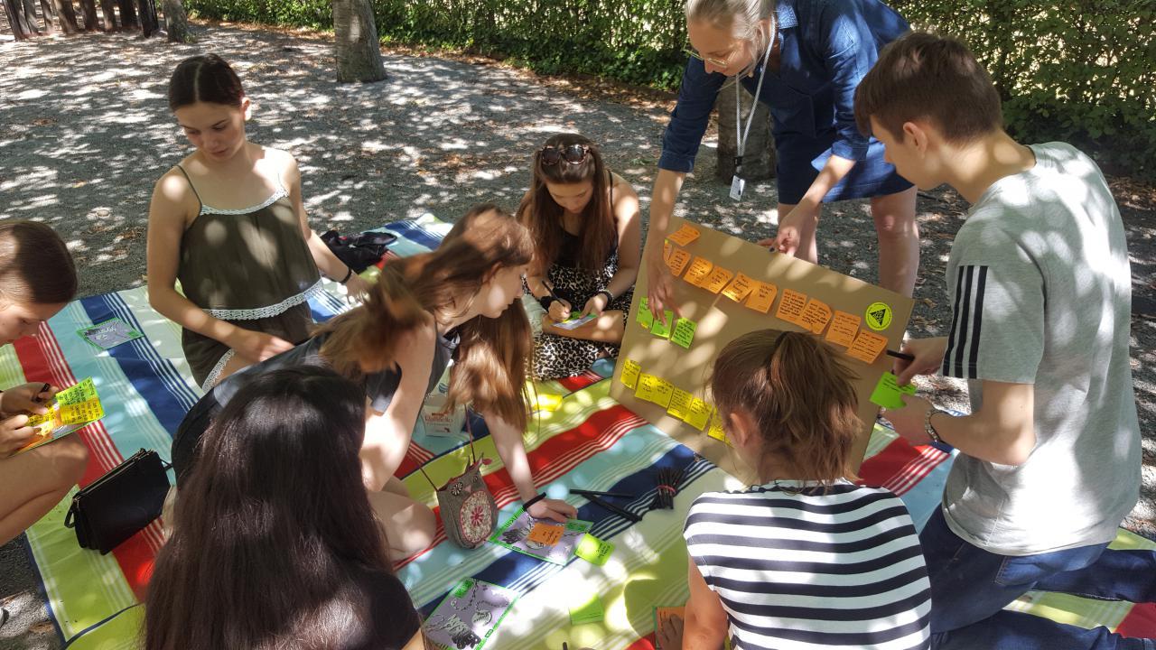 Eine Gruppe von Jugendlichen sitzt auf einer Picknick-Decke im Freien und hören einer Frau zu, die mit ihnen spricht.