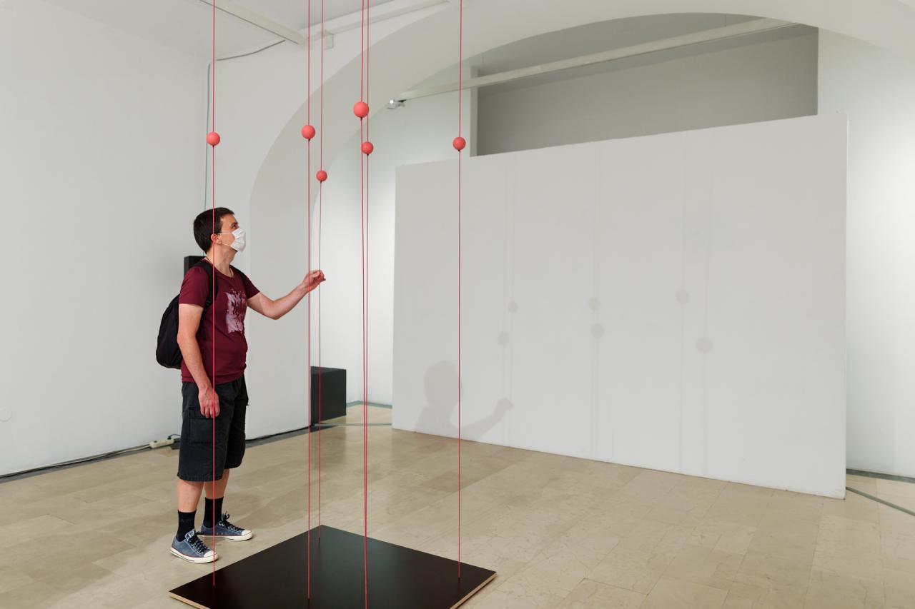 Ein Mann fasst ein Kunstwerk der Ausstellung »Is it working?« an, das aus Schnüren besteht, die zwischen der Decke und dem Boden gespannt sind.