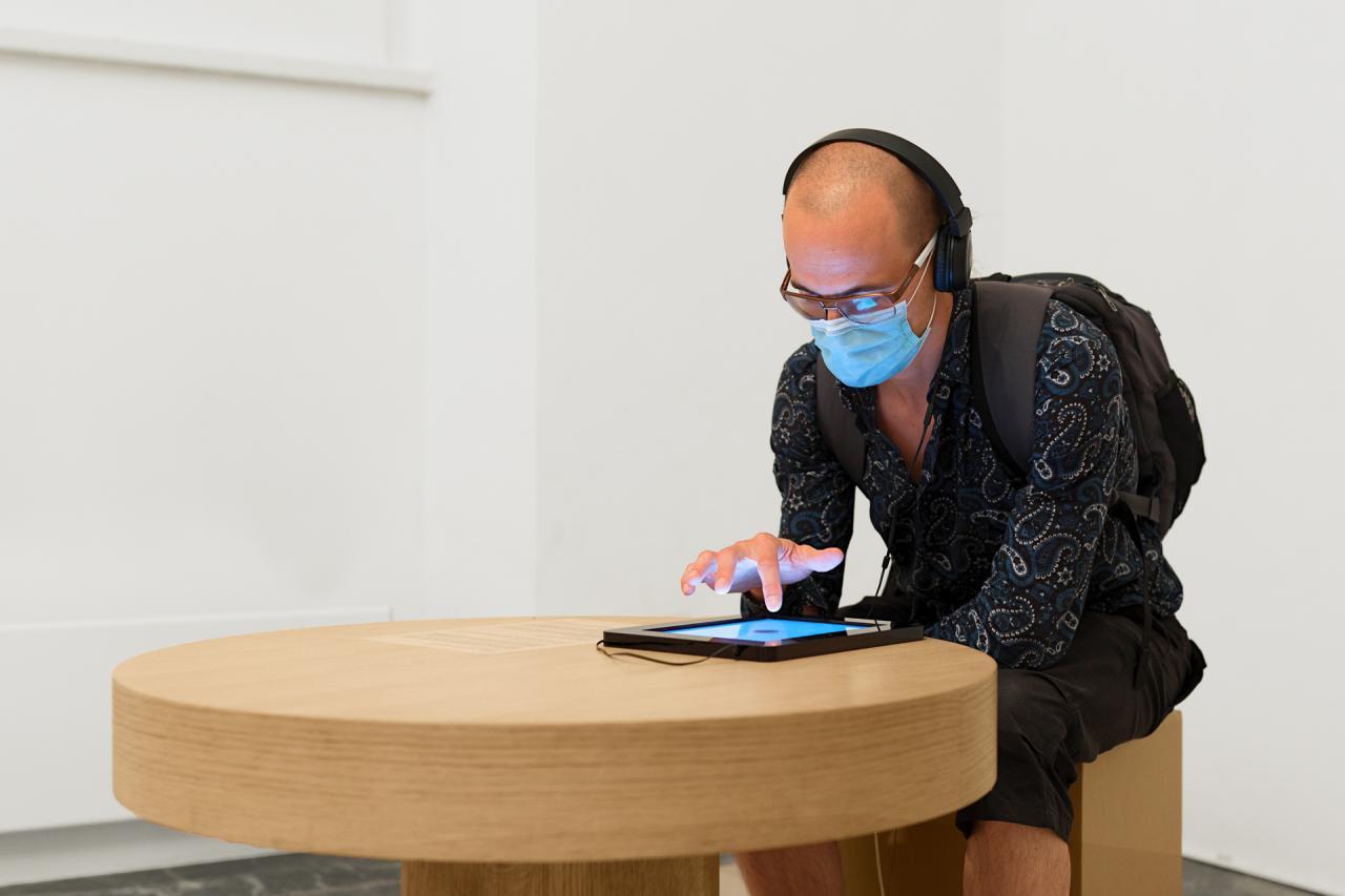 Ein Mann sitzt an einem Tisch. Er bedient ein Tablet, das vor ihm auf dem Tisch liegt.
