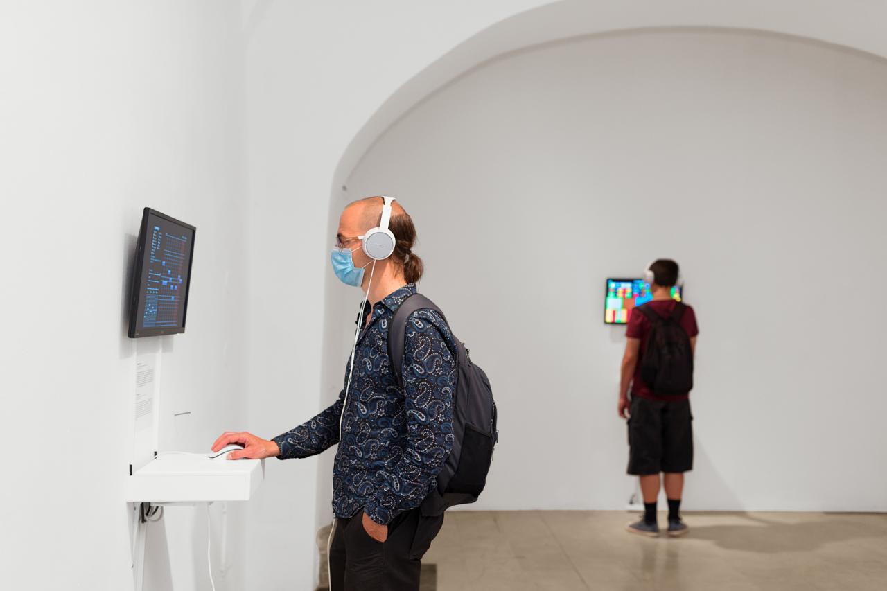Ein Mann steht vor einem Bildschirm, der an der Wand hängt. Er nutzt die Computermaus, die unter dem Bildschirm auf einem Tisch liegt.