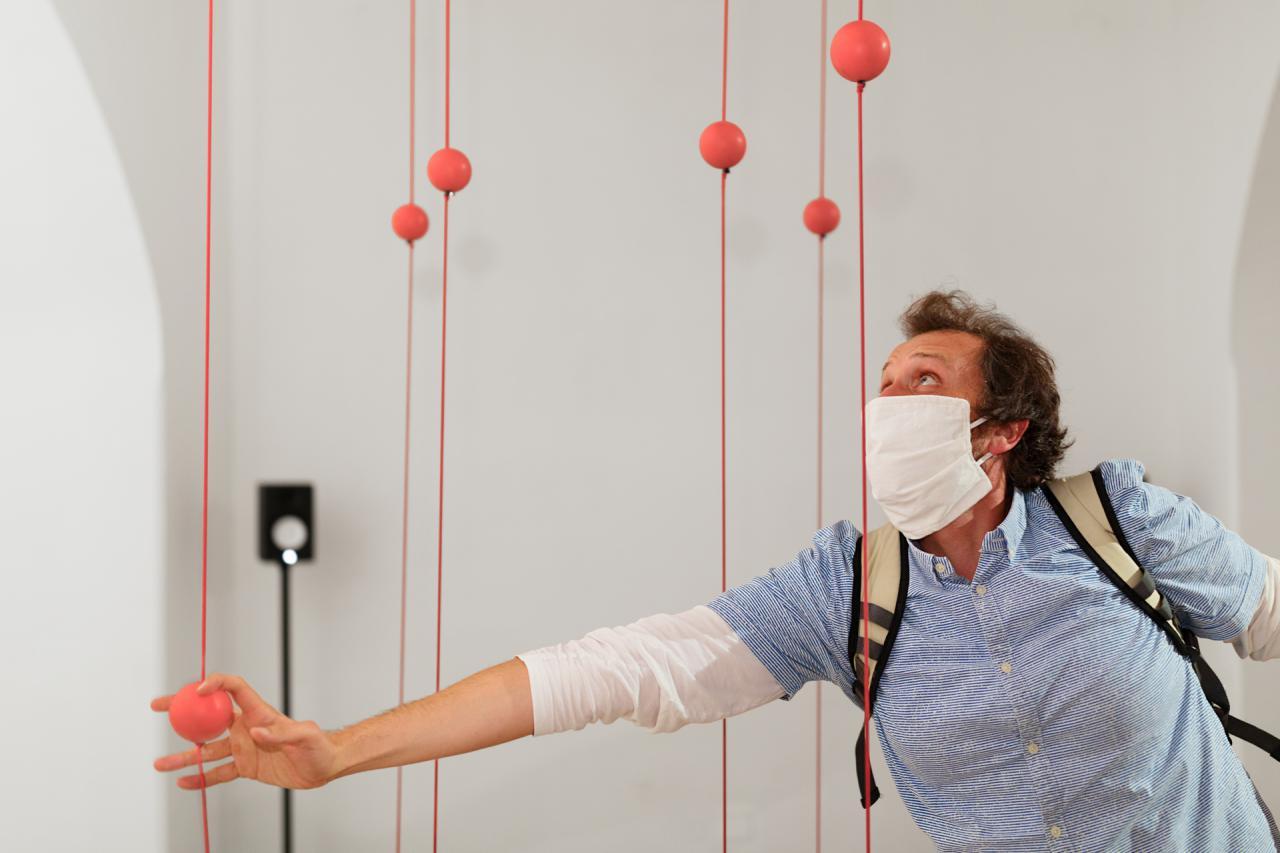 Ein Mann fasst eine Kugel an, die an einem Seil befestigt ist, das zwischen der Decke und dem Boden gespannt ist.