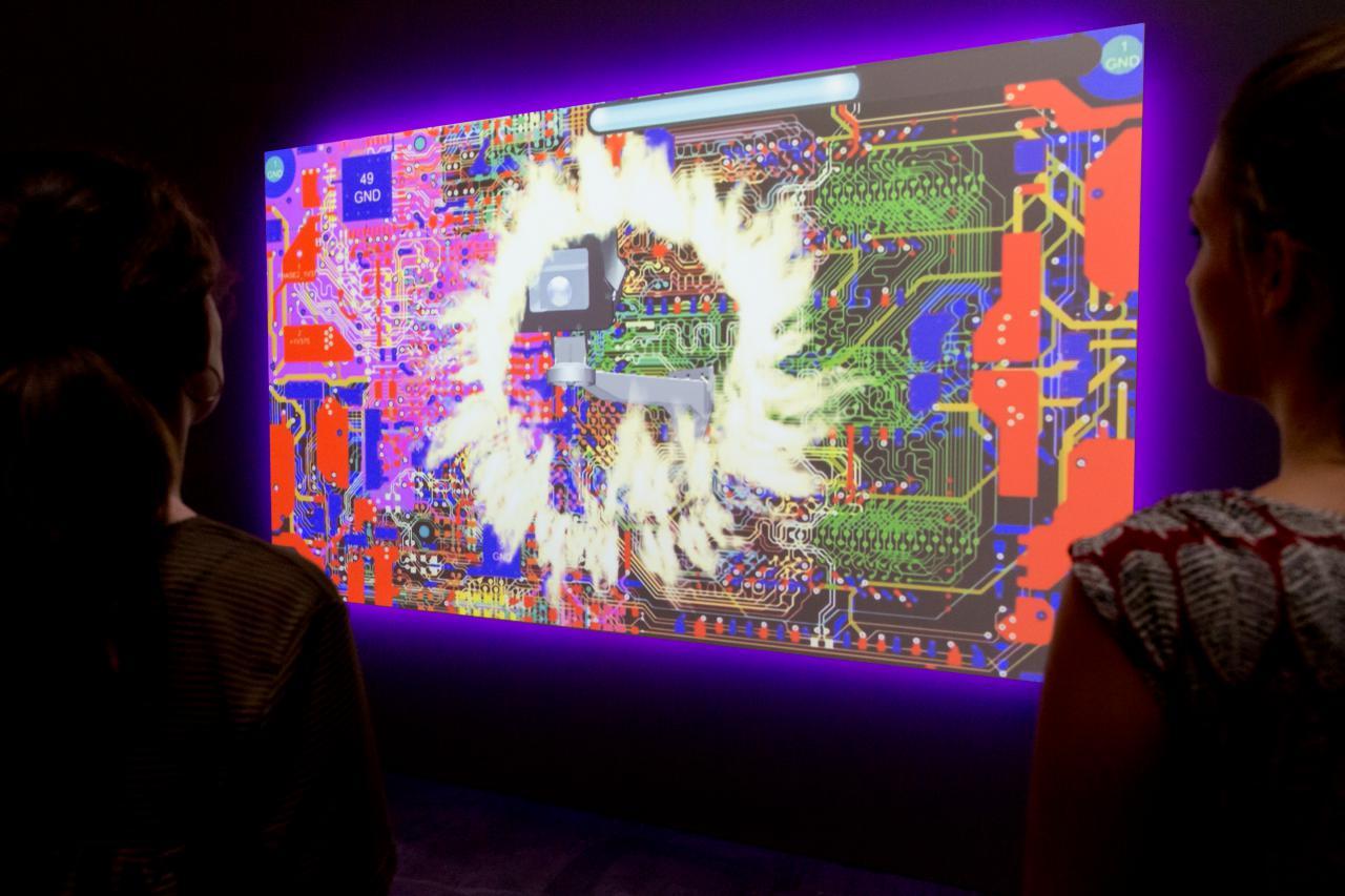 Zwei Besucherinnen betrachten ein Video-Kunstwerk, das eine Collage aus Computer-Hardware und Flammen zeigt