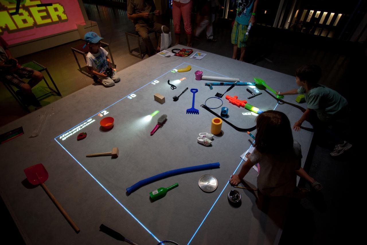 Kinder sitzen vor einer Spielfläche auf der Gegenstände liegen und virtuelle Autos fahren