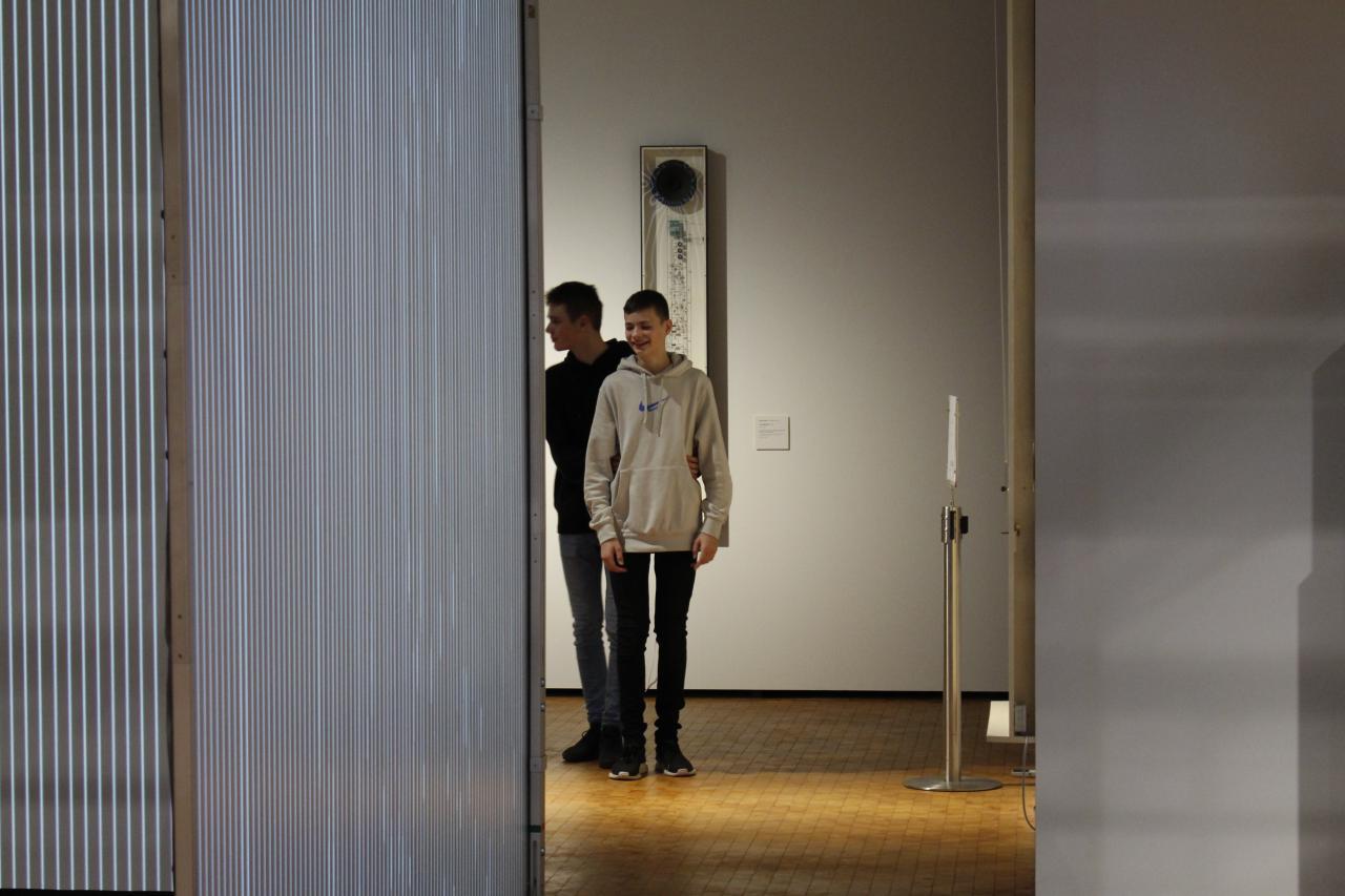 Zwei Jungs laufen mit geschlossenen Augen durch die Ausstellung »Writing the History of the Future«.