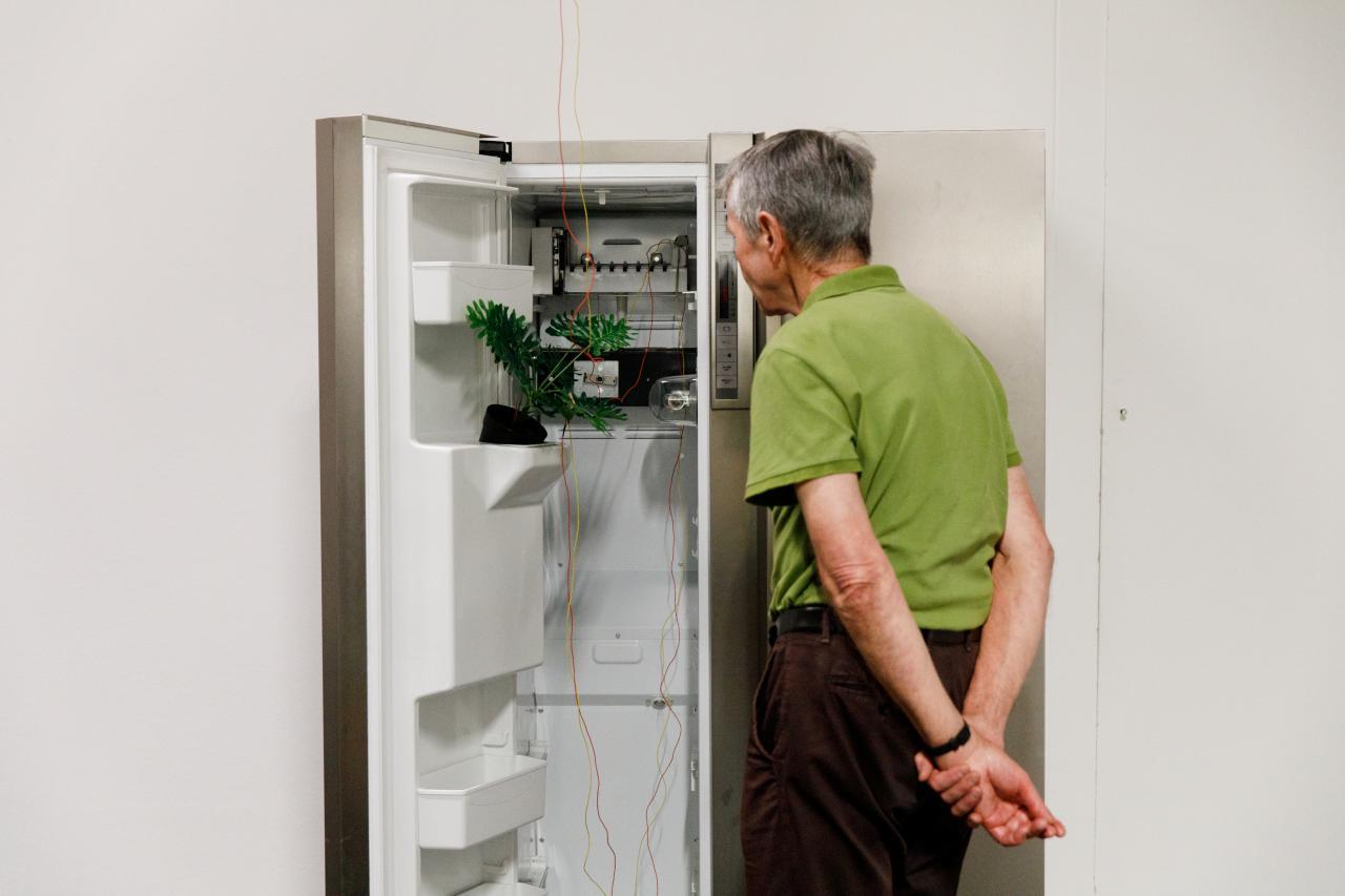 Zu sehen ist ein älterer Herr vor einem offenen Kühlschrank, der als Medieninstallation umgewandelt wurde.